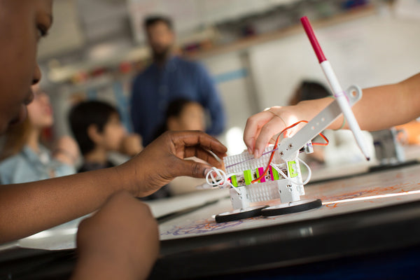 A boy builds a littleBits Doodle Wizard invention in his classroom.