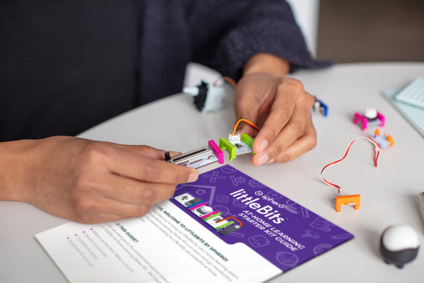 A person snaps together pink and green littleBits at a white table with a getting started guide nearyby.