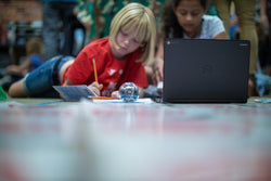 Two young girl students work together on a project using a laptop and Sphero BOLT.