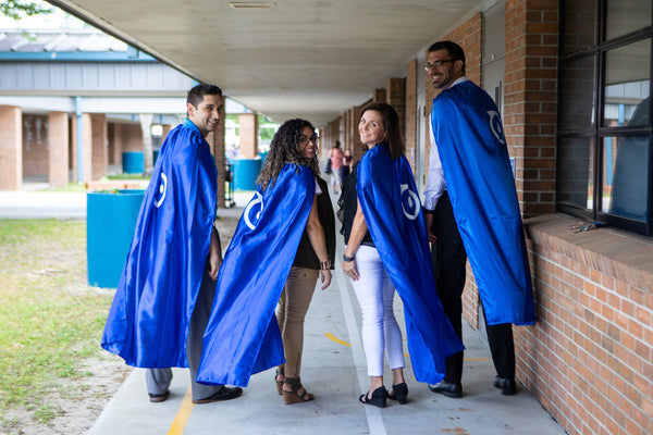 Teachers wearing blue Sphero Super Hero capes.