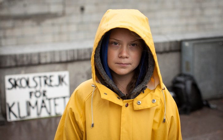 Child in yellow rain jacket looking at camera.