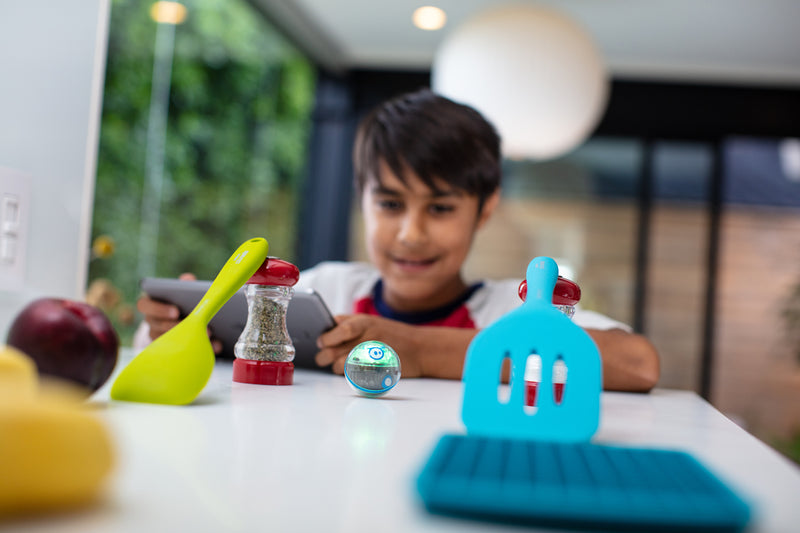 A boy drives his Sphero Mini across the kitchen table through obstacles created out of cooking utensils.