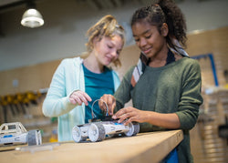 Two teenage girls work together in a makerspace to build an invention on top of their Sphero RVR.