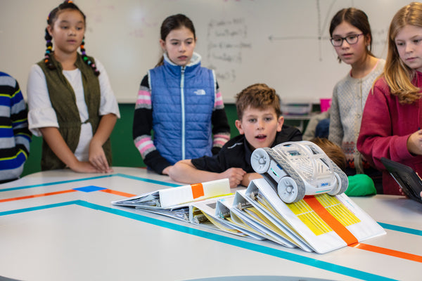 A class of elementary school kids look on as Sphero RVR traverses a pile of books.