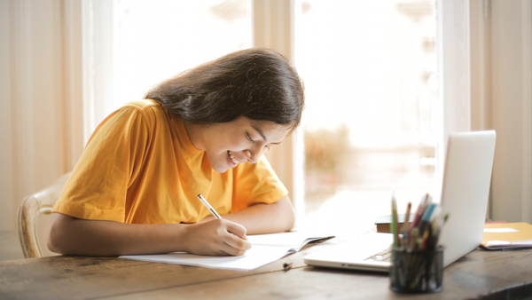 A girl in a yellow shirt works at her desk at home with a laptop and notepad.