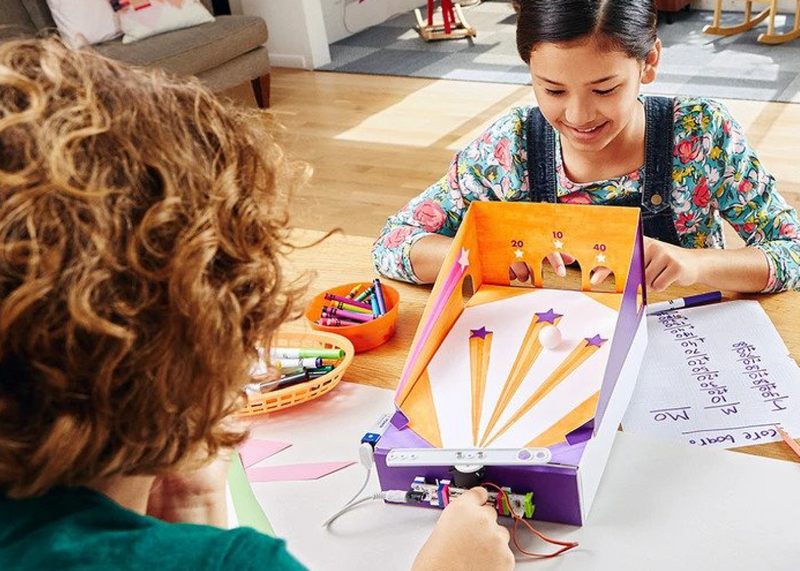 A boy and a girl build a pinball game out of littleBits and craft materials.