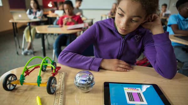 A girl in a purple sweatshirt sits at her desk coding her Sphero BOLT on a tablet.