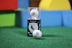 The Sphero Mini Golf in its packaging and out sitting on green turf.