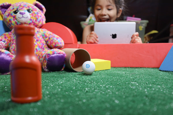 A young girl codes her Sphero Mini Golf ball with a tablet.