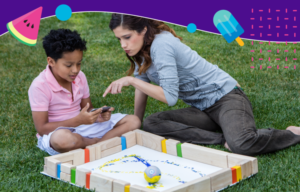 A boy and woman sit in the grass outside painting with a Sphero robot.