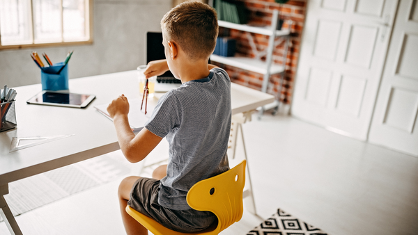 A boy sits at his desk at home and works independently on an assignment.