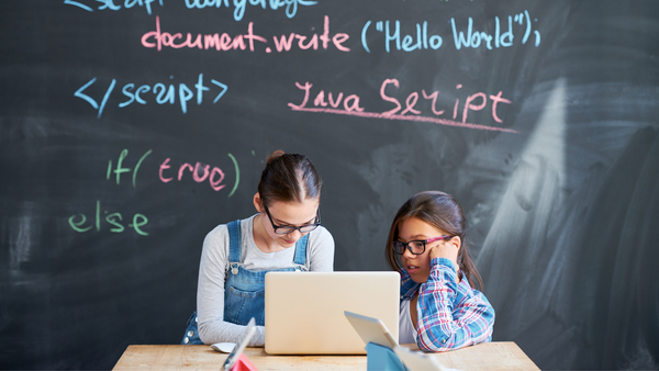 Two girls work together on a laptop; Javascript text is on the chalkboard behind them.