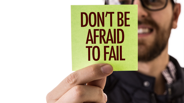 "A man holds a small sign that reads ""Don't be afraid to fail."""