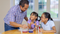 A father and his two daughters work on a science activity at the kitchen table.