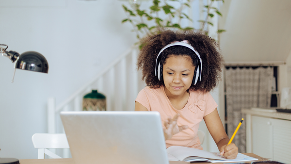 A girl wearing headphones works through her hybrid learning classes on her laptop at home.