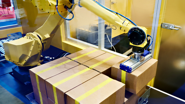 An industrial robot packs boxes in a warehouse.