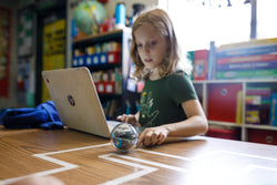 A girl programs her Sphero BOLT with a laptop by herself.