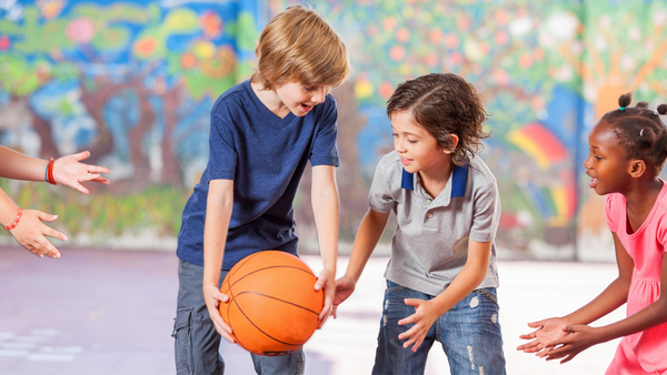 Two boys and a girl pass a basketball to each other in gym class.