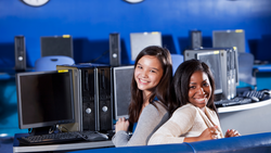 Two teenager girls sit together back to back in a computer lab at school.