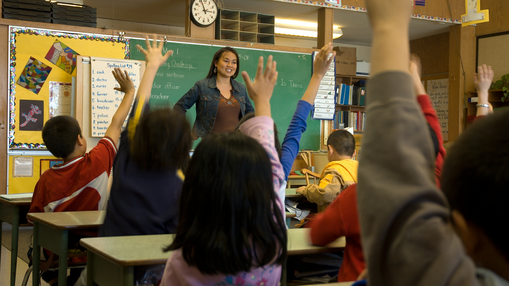 A teacher stands in front of her class while they raise their hands to answer questions.