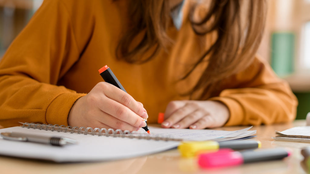 A girl sits at her desk and takes notes with markers and a notepad.
