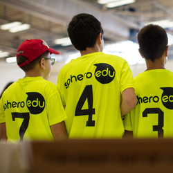 Group of boys wearing Sphero Edu bright yellow shirts.