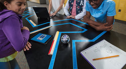 Students around table with STEAM robot being programed through a maze.