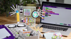 A desk with a littleBits storage case, STEAM invention and code on a laptop.