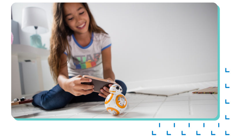 Girl in her room playing with her Sphero BB-8.