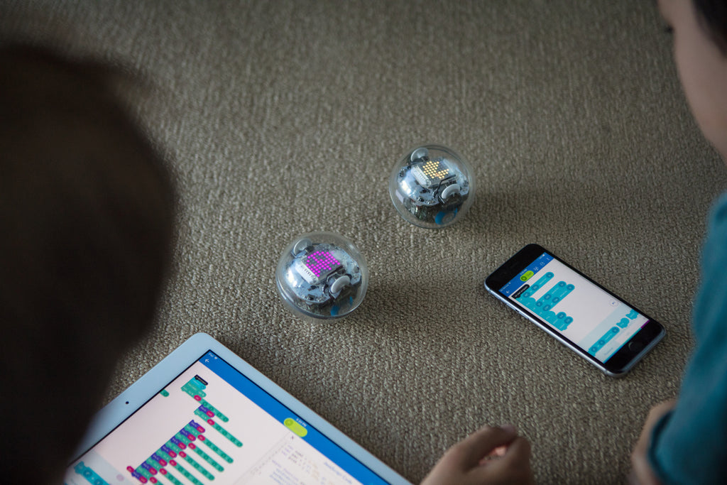 Two kids use block coding on a tablet and smartphone to code their Sphero BOLT programmable robots.