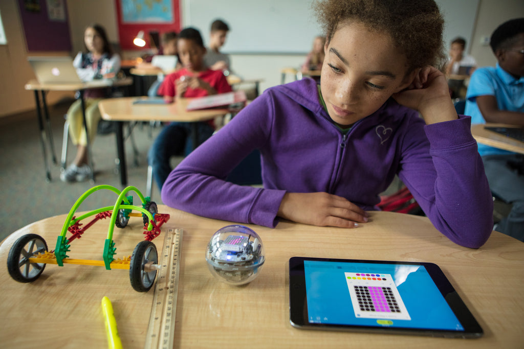 A girl sits at her desk in a classroom looking at Sphero BOLT and programming it on a tablet.