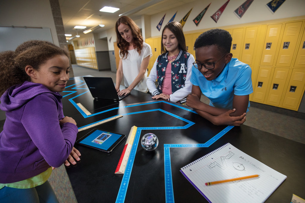 Students gather around a table while they code a Sphero BOLT for National Robotics Week.