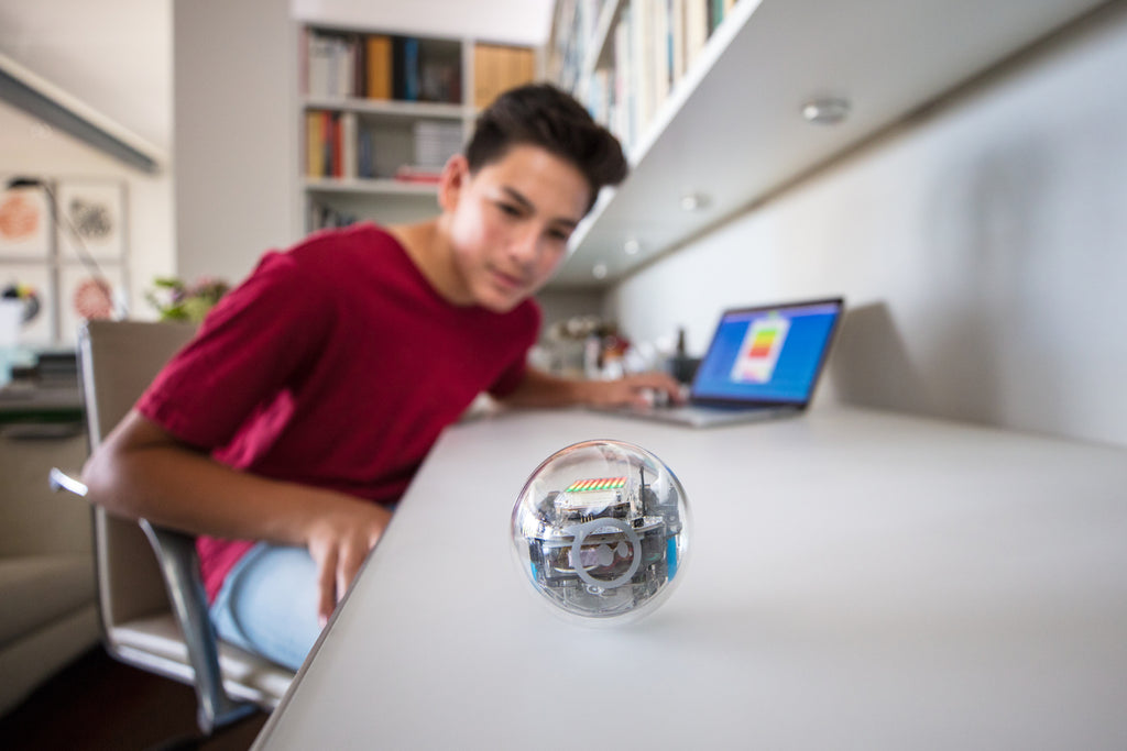 A teenage boy codes his Sphero BOLT at his desk with a laptop.