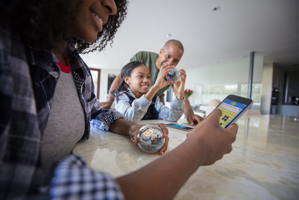 A girl and her parents sit at the kitchen counter programming a Sphero BOLT with a smartphone.