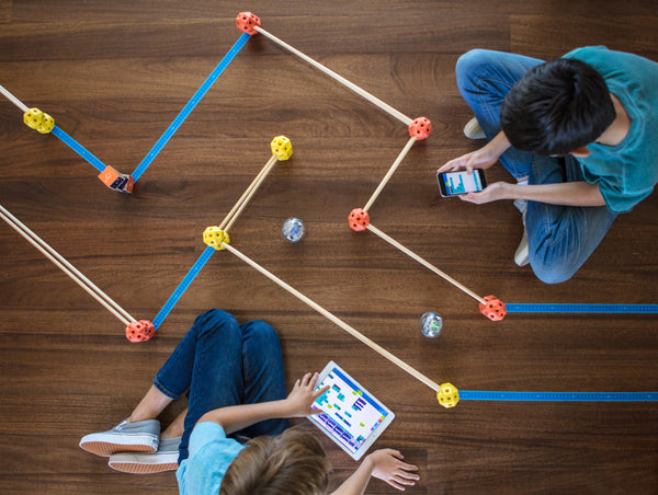Two boys sitting on a floor moving Sphero BOLTs through a maze using block-based coding.
