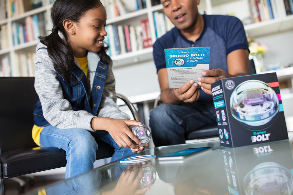 A girl and her dad play with a Sphero BOLT at home.