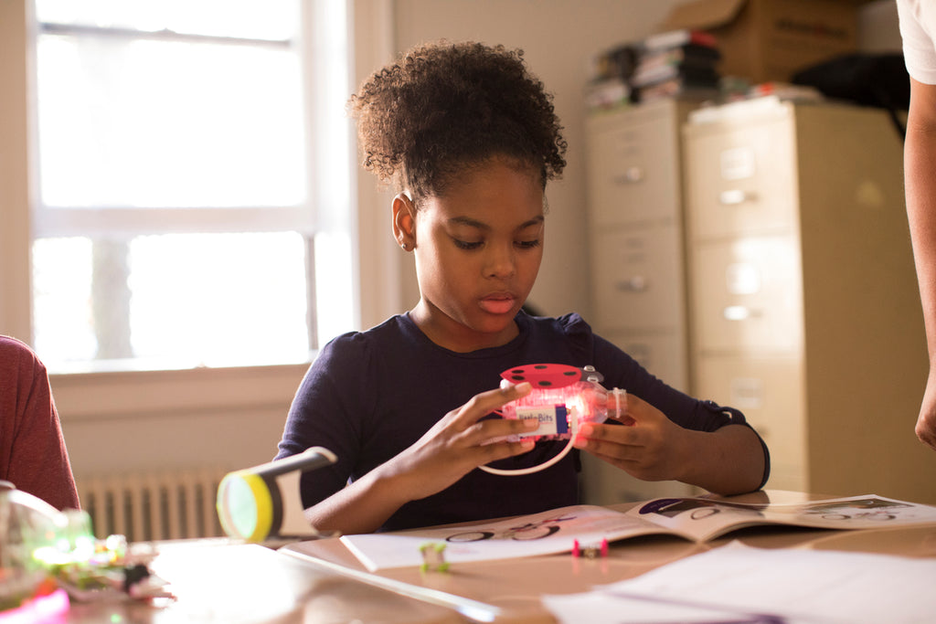 A girl sits at her desk building an invention out of littleBits and craft supplies.