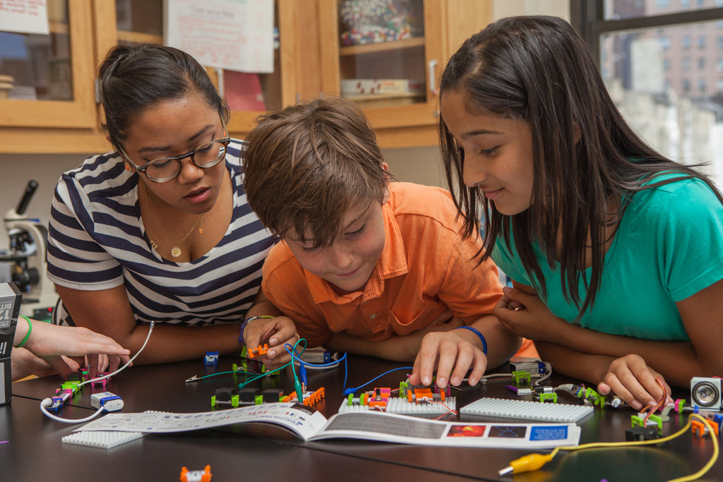 Three students look over a littleBits invention in their classroom.