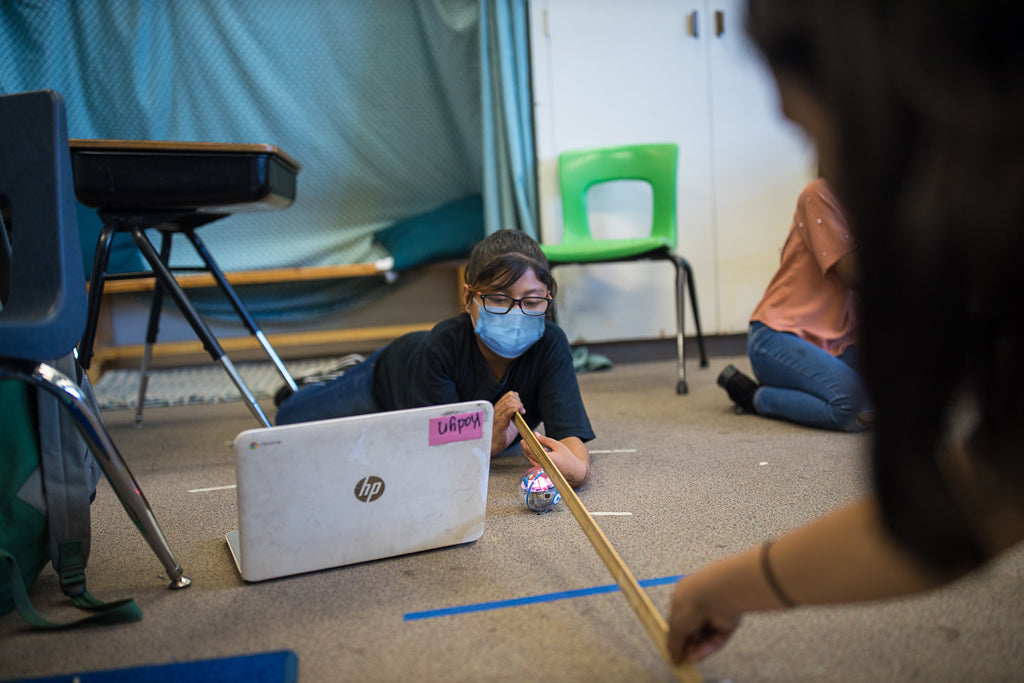 A girl lies on the floor near her laptop while wearing a mask and measuring distance with a yard stick.
