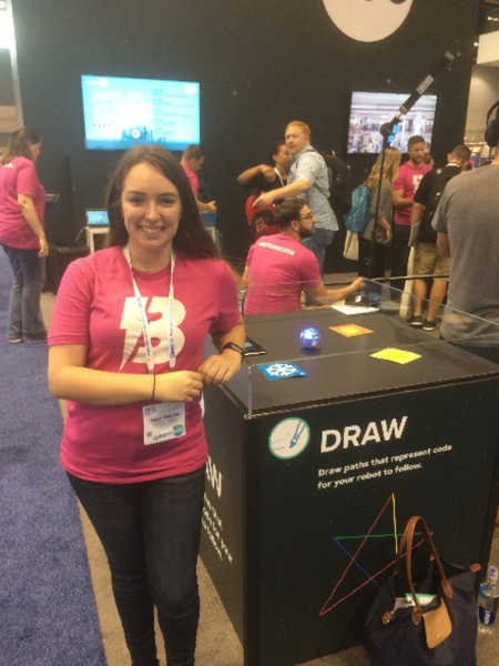 Woman standing by Sphero display with pink BOLT shirt on.