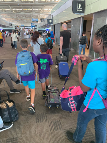Students and teachers walking through airport together.