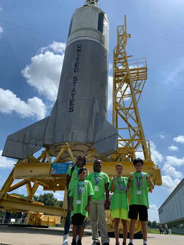 Students posing in front of spaceship.