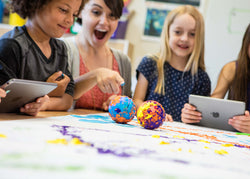 An excited teacher and students pointing to a robot ball covered in paint.