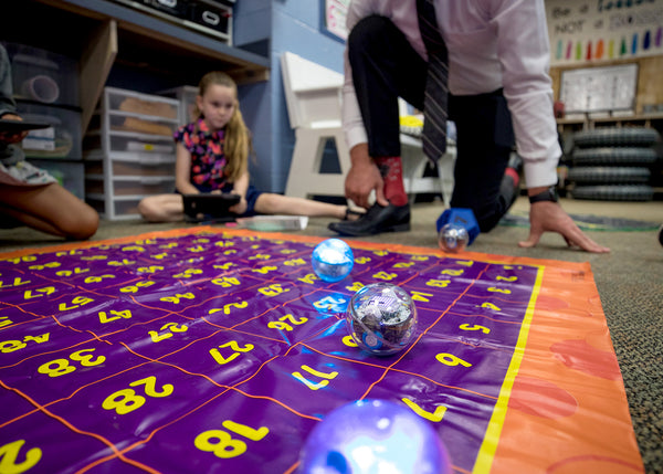 A teacher and students sitting on the floor playing a shapes and numbers game with robot toys balls.