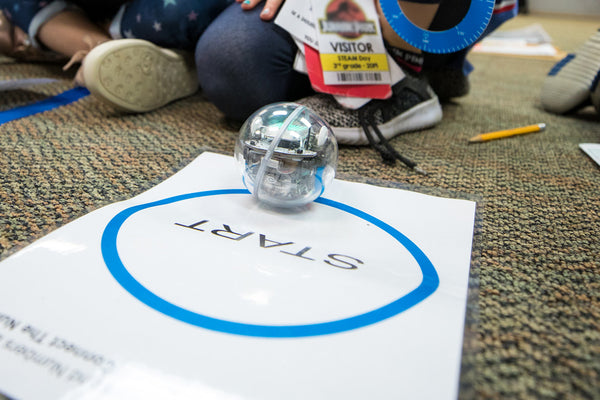 Sphero Bolt sitting on a white piece of paper that says START