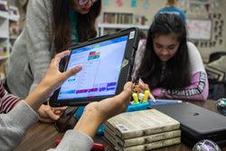 Students coding on a Ipad in a library while collaborating with a teacher
