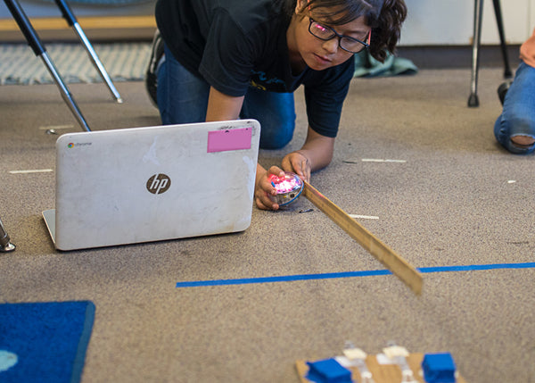 Girl with laptop kneeling on the floor with STEAM robot and ruler.
