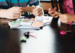 A girl and boy inventing with electronic snap-together building blocks.