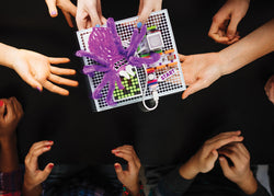 Kid's hands holding a littleBit's spider invention.