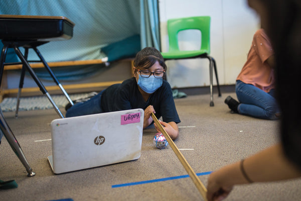 Student wearing mask holding a ruler while programming Sphero STEM robot.